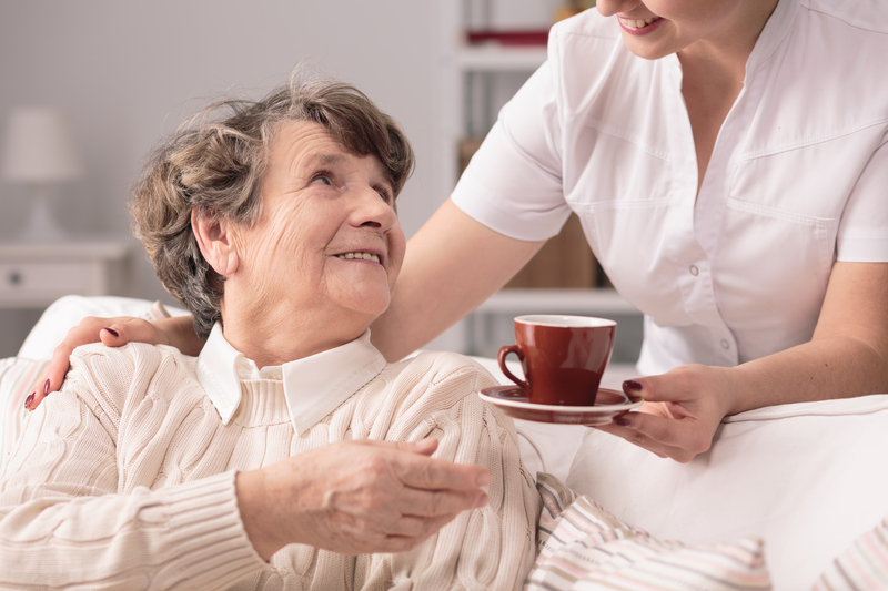 Nursing Assistant Handing Resident Cup Of Tea